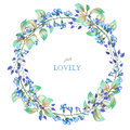 A floral circle frame (wreath) of the watercolor blue flowers and green leaves, a place for a text Royalty Free Stock Photo