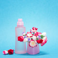Floral fragrance pink glass perfume bottle and bouquet of small paper flowers in its cap on blue background copy space Stock Photo