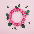 Floral frame made of pink rose flowers and green leaves on pastel background top view. Flat lay. Fashion and creative composition Royalty Free Stock Photo