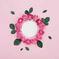 Floral frame made of white blank, pink rose flowers and green leaves on pastel background top view. Flat lay styling. Royalty Free Stock Photo