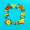 Floral frame made of yellow and red flowers with petals on blue background. Flat lay, top view. Floral background. Royalty Free Stock Photo