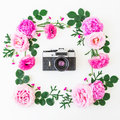 Floral frame of pink flowers and old retro camera on white background. Floral lifestyle composition. Flat lay, top view. Royalty Free Stock Photo
