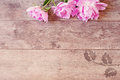 Floral frame with pink peonies on wooden background. Styled marketing photography. Copy space.