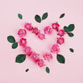 Floral heart made of pink rose flowers and green leaves on pastel background top view. Flat lay styling. Fashion composition.