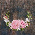 Floral wreath with pink peony flowers, feathers at wooden texture. Greeting card in vintage boho style. Watercolor