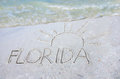 Florida and sun drawn in sand on beach with a wave drawing the at the of over it colorful coming from the top representing Stock Photography
