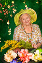 Florist beautiful older woman sitting in the garden among the flowers Stock Photo