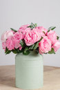 Florist did rich bunch flowers light background, wooden surface. green vase Royalty Free Stock Photo