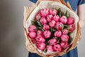 Florist girl with peony flowers or pink tulips Young woman flower bouquet for birthday mother's day. Royalty Free Stock Photo