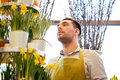 Florist man with narcissus flowers at flower shop people business sale and floristry concept Royalty Free Stock Image