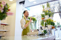 Florist man or seller at flower shop counter people sale retail business and floristry concept happy smiling with cashbox standing Stock Photography