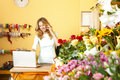 Florist portrait of middle age standing at her flower shop and using her telephone and laptop to take orders for her store Royalty Free Stock Image