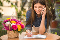 Florist portrait of young female talking on phone and making notes at flower shop Stock Photo