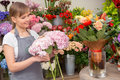 Florist puts bouquet into the vase new floral wonder young smiling holds flowers making a new floral arrangement Stock Photography