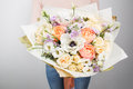 Florist at work. Make rich bouquet diferent color and flowers. Bunch in their hands Royalty Free Stock Photo