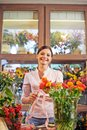 Florist at work pretty looking camera while working with fresh flowers Stock Photo