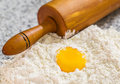 Flour egg yolk and rolling pin iii pastry making preparation with on a granite counter surface Stock Photo