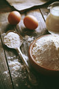 Flour and eggs on a wooden table Stock Photography