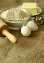 Flour, oil, eggs and rolling pin on sacking Stock Photos