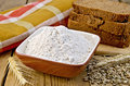 Flour rye in bowl with bread on board Royalty Free Stock Photo
