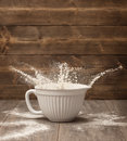 Flour splash flying out of a white mixing bowl in the kitchen Royalty Free Stock Photography