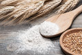 Flour in a wooden spoon and wheat grains Royalty Free Stock Photo