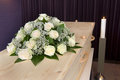 Flower arrangement on coffin a a and a burning candle the background in a mortuary Royalty Free Stock Photography