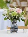 Flower arrangement in pitcher old silver Royalty Free Stock Images