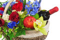Flower arrangement of roses orchids fruits and bottle of wine in basket isolated on white background closeup Royalty Free Stock Images