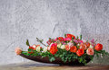 Flower arrangement in wooden tray close up rose and carnation on table beside grunge concrete wall Royalty Free Stock Photo