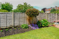 Flower bed in the back-garden with a fence behind the plants. Royalty Free Stock Photo