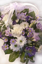 Flower bouquet in a basket with a lace ribbon beautiful of white lilac and purple flowers Royalty Free Stock Images