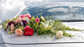 Flower decoration and a ring set on gray wedding car bonnet.