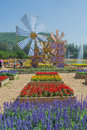 Flower farm with wooden wind turbine. Royalty Free Stock Photo