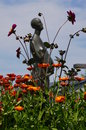 Flower garden a in full bloom with a statue of a women in the background Stock Photo