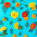 Flower pattern of yellow and red flowers with leaves on blue background. Flat lay, top view. Floral background. Royalty Free Stock Photo