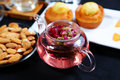 Flower tea afternoon include a glass teapot of some almonds and cakes Royalty Free Stock Images
