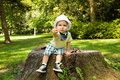 A flower for you adorable toddler offering while sitting on stump Royalty Free Stock Images