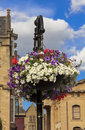 Flowerpot with colorful flowers hanging from ornamental lantern street decoration in oxford england historic buildings and Royalty Free Stock Photography