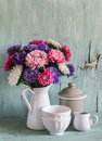 Flowers asters in a white enameled pitcher and vintage crockery - ceramic bowl and enameled jar, on a blue wooden background. Royalty Free Stock Photo