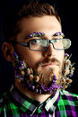Flowers in beard handsome young man spectacles and a of black background Stock Photos