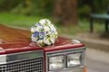 Flowers on bonnet wedding bouquet red car Royalty Free Stock Image