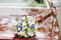 Flowers on bonnet wedding bouquet surface of red car Royalty Free Stock Images