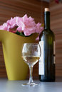 Flowers a bottle and a glass of wine white on the table Royalty Free Stock Photography