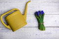 Flowers bouquet with watering can on wooden table. Top view Royalty Free Stock Photo