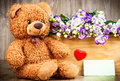 Flowers in the box and a teddy bear