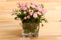 Flowers bunch of small pink roses in a glass vase over a wooden table Stock Photos