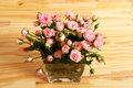 Flowers bunch of small pink roses in a glass vase over a wooden table Stock Photography