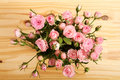 Flowers bunch of small pink roses in a glass vase over a wooden table Royalty Free Stock Image