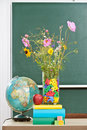 Flowers in a classroom vase decorated with alphabetical letters with an apple and globe on teachers desk front of board Royalty Free Stock Photography